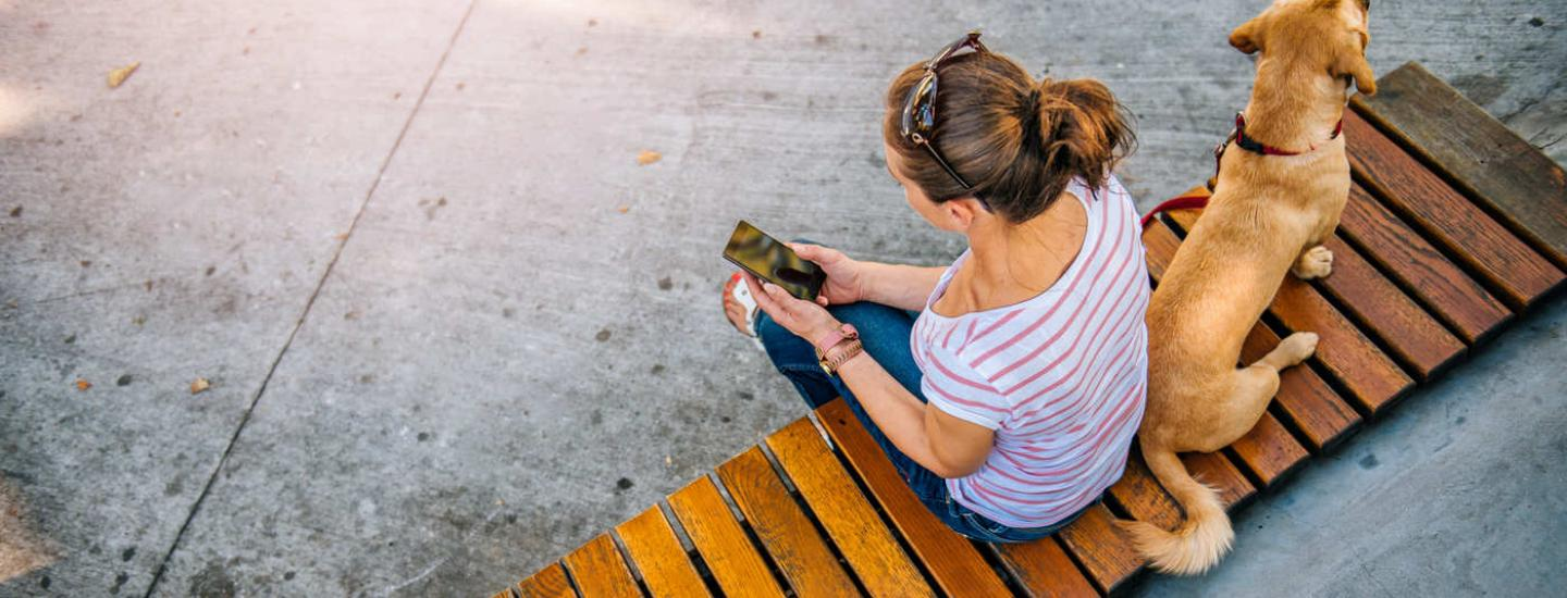 Woman sitting with a dog on a bench outside using her cell phone