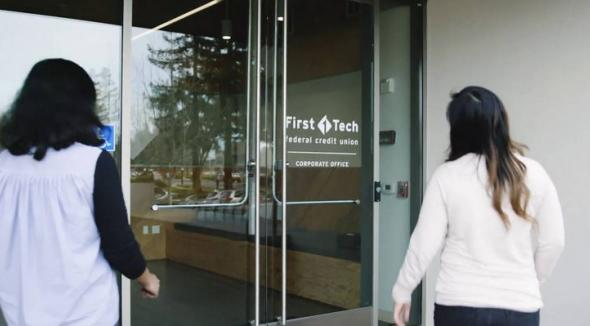 two females walking into a first tech bank