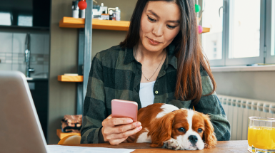 brunette girl looking at phone with dog in lap