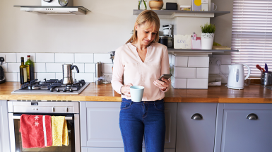 woman in kitchen holding coffee looking on mobile phone