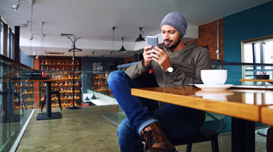 Man in coffeeshop on looking at mobile phone