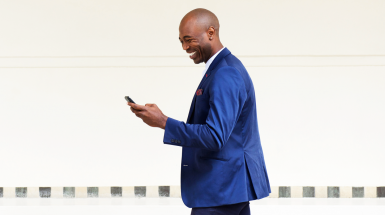 man in suit laughing at mobile phone
