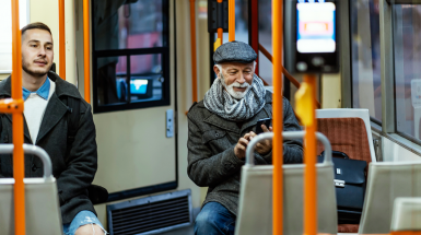 young and old man on subway looking at mobile phone