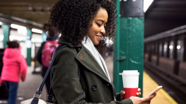 girl waiting for subway looking at mobile phone with a coffee